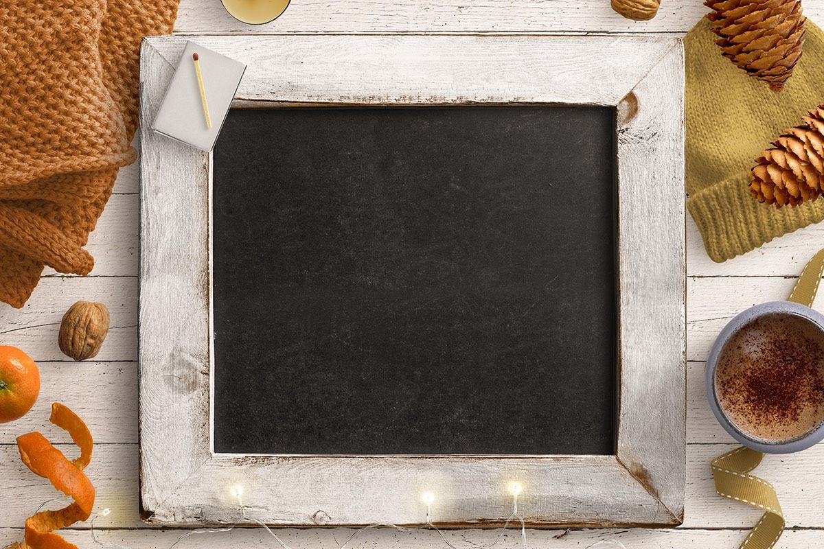 Cozy Winter Blackboard Scene with Fairy Lights Woollen items pinecones and hot drink