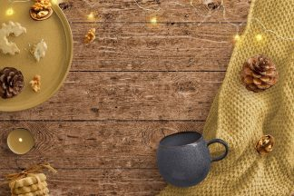 Cozy Winter Scene with Fairy Lights Blanket Biscuits and Mug on Wooden background
