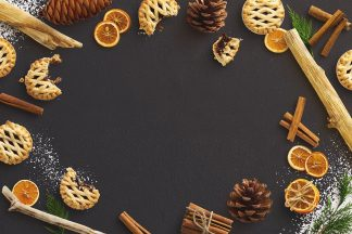 Winter Baking Scene with Mince Pies Cinnamon Sticks Dried Oranges and Pinecones.